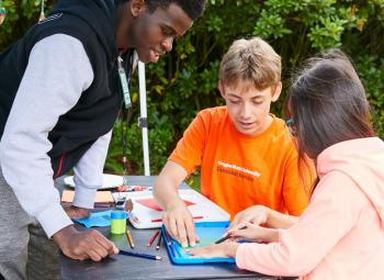 A Youth Environmental Educator (left) works on an activity with children in 2019.